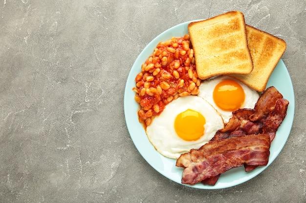 Tradizionale colazione inglese completa con uova fritte, fagioli, pancetta e pane tostato