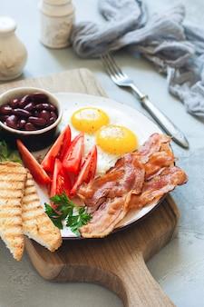 Colazione inglese completa tradizionale con uova fritte, salsicce, fagioli, pomodori grigliati e pancetta su sfondo grigio cemento. vista dall'alto