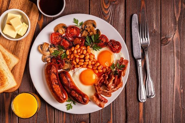Tradizionale colazione inglese completa con uova fritte, salsicce, fagioli, funghi, pomodori grigliati e pancetta su fondo in legno