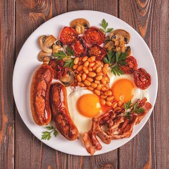 Tradizionale colazione inglese completa con uova fritte, salsicce, fagioli, funghi, pomodori grigliati e pancetta su fondo di legno