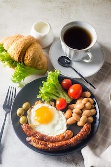Colazione inglese completa tradizionale con uova fritte, salsicce, fagioli, pomodori su un piatto, croissant e caffè su sfondo grigio. vista dall'alto
