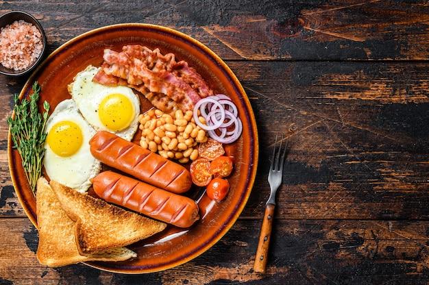 Tradizionale colazione inglese completa con uova fritte, salsicce, pancetta, fagioli e toast. fondo in legno scuro. vista dall'alto. copia spazio.