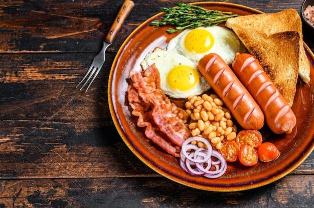 Tradizionale colazione inglese completa con uova fritte, salsicce, pancetta, fagioli e toast. tavolo in legno scuro. vista dall'alto.