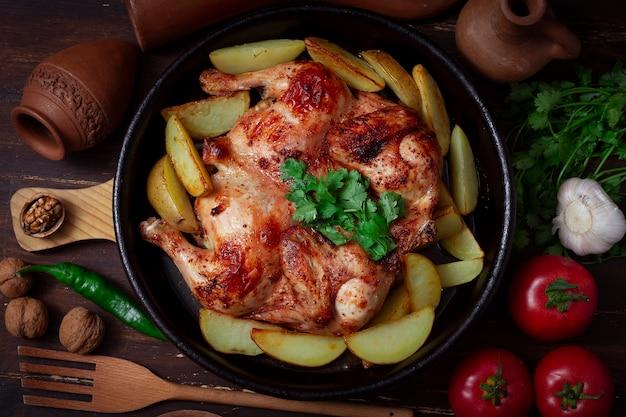 Piatto tradizionale georgiano, pollo al tabacco, con patate, su un tavolo di legno, vista dall'alto.