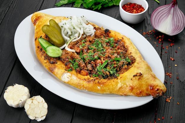 Torta aperta georgiana tradizionale con carne. carne macinata con cipolle e spezie, cotta nel pane georgiano su sfondo scuro con erbe e spezie. cibo delizioso a pranzo.