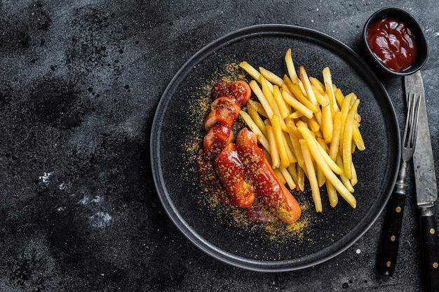 Currywurst tedesco tradizionale, servito con patatine fritte. tavolo nero. vista dall'alto. copia spazio.