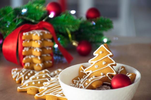 Pan di zenzero tradizionale a forma di albero di natale nel piatto bianco e pila di biscotti dei fiocchi di neve con i giocattoli rossi dei rami dell'abete del nastro rosso su fondo