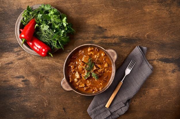 Carne di gulasch tradizionale in ciotola di ceramica con forchetta di pepe ed erbe e tovagliolo vista dall'alto spazio copia