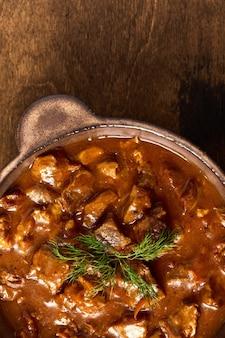 Carne di gulasch tradizionale in una ciotola di ceramica con vista verticale di fuoco selettivo macro a macroistruzione di erbe e pepe