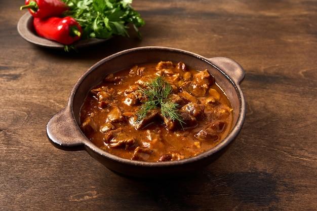 Carne di gulasch tradizionale in ciotola di ceramica su fondo di legno marrone con pepe ed erbe da vicino