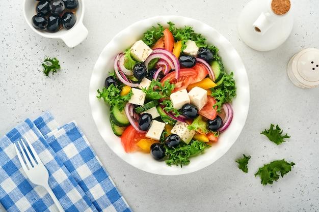 Insalata greca tradizionale di cetriolo fresco, pomodoro, peperone dolce, lattuga, cipolla rossa, formaggio feta e olive con olio d'oliva su piatto bianco. cibo sano, vista dall'alto.