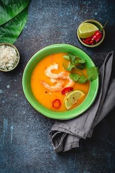 Zuppa tailandese sana tradizionale tom yum con gamberetti, lime, coriandolo in ciotola su fondo rustico con riso bianco, colpo dall'alto. autentico concetto di cibo tailandese con copia spazio