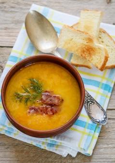 Tradizionale zuppa di piselli fatta in casa con pancetta, erbe e crostini. stile rustico