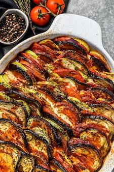 Ratatouille di verdure fatte in casa tradizionale al forno nel piatto. sfondo grigio. vista dall'alto.