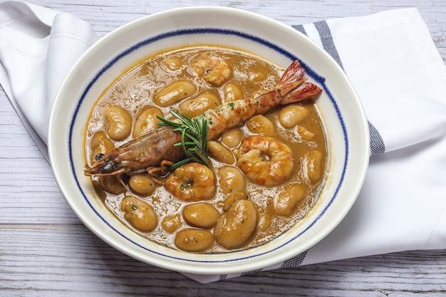 Spezzatino di fagioli bianchi fatti in casa tradizionale con gamberi. cucina tipica spagnola. sulla tavola di legno
