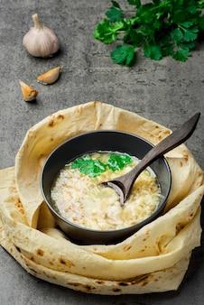 Zuppa khash calda tradizionale in una ciotola, vista dall'alto. piatto orientale tradizionale armeno, turco o caucasico - khash, con coriandolo fresco, aglio e pane lavash essiccato