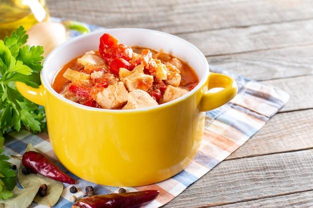 Pollo alla paprika ungherese tradizionale, noto anche come paprikash di pollo in salsa di panna acida succosa e prezzemolo su fondo di legno