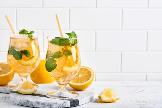 Tè freddo tradizionale con limone e ghiaccio in bicchieri alti su sfondo tavolo in marmo tè freddo al limone. messa a fuoco selettiva. bevanda fresca estiva rinfrescante.