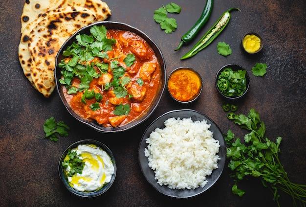 Piatto tradizionale indiano pollo tikka masala con carne di curry piccante in una ciotola, riso basmati, pane naan, salsa raita allo yogurt su fondo rustico scuro, vista dall'alto, primo piano. cena in stile indiano dall'alto