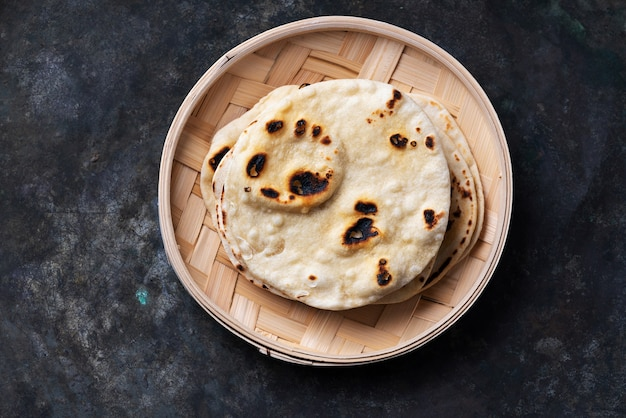 Tradizionale indiana chapati con focaccia su un vassoio di bambù. facile concetto di cucina casalinga. vista dall'alto. lay piatto.