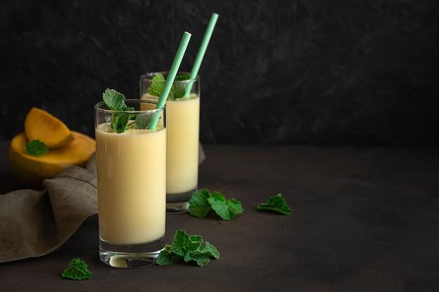Drinklassi di latte indiano tradizionale con mango su una parete scura