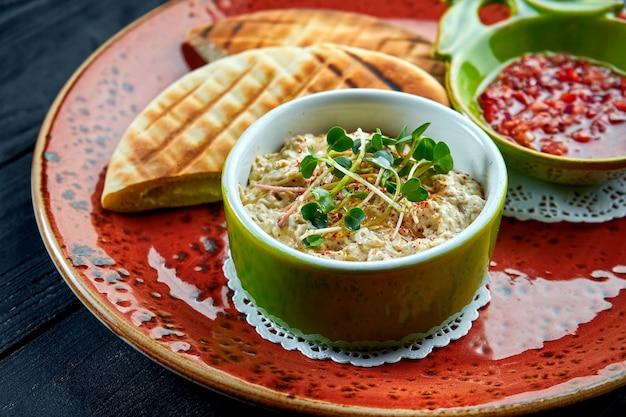 Baba ghanoush tradizionale israeliano o orientale con salsa di verdure e pita, servito in un piatto rosso su un tavolo di legno