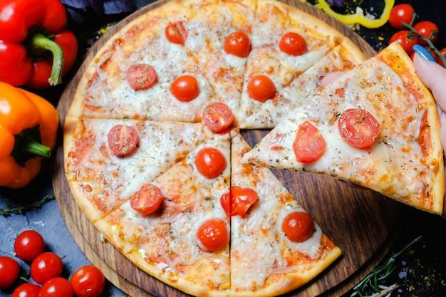 Cucina tradizionale italiana. deliziosa fetta di pizza con formaggio fuso e pomodorini