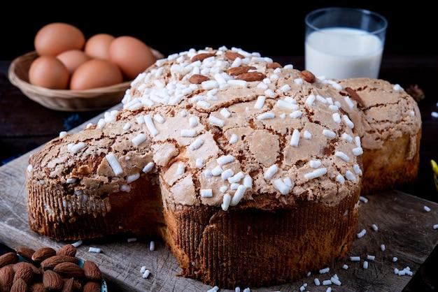 Dolci della tradizione italiana per pasqua - colomba pasquale. pasticcini festivi con mandorle e zucchero a velo superficie scura decorazioni pasquali e uova