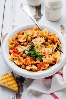 Piatto tradizionale italiano, zuppa, zuppa, pasta e ceci serviti in un vecchio piatto su un vecchio fondo di legno wooden