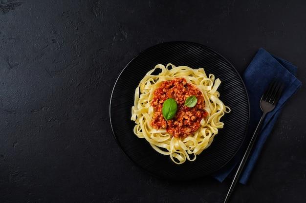 Fettuccine di piatto tradizionale italiano con salsa bolognese, basilico e parmigiano in banda nera su superficie di legno scuro