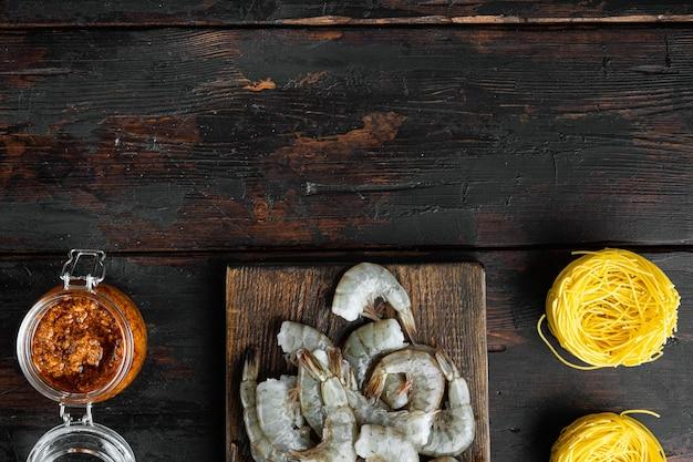 Piatto della tradizione italiana. pasta con pesto di ricotta parmigiano e set di ingredienti di pesce alla griglia, su un vecchio tavolo di legno scuro, vista dall'alto piatta, con copia spazio per il testo