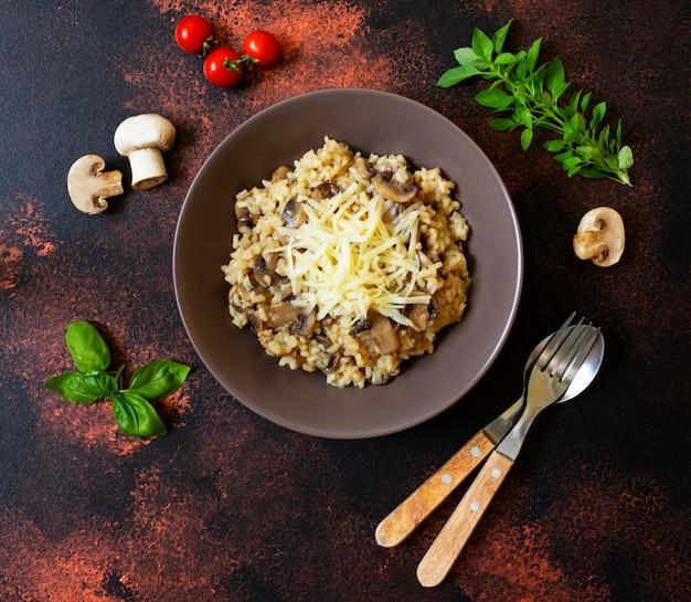 Piatto italiano tradizionale di risotto all'arborio di riso con funghi. servito con basilico fresco, funghi e pomodorini. vista dall'alto. sfondo rustico scuro. spazio per il testo