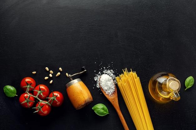 Sfondo di cibo italiano tradizionale con spaghetti pomodori formaggio olive e olio su sfondo scuro.