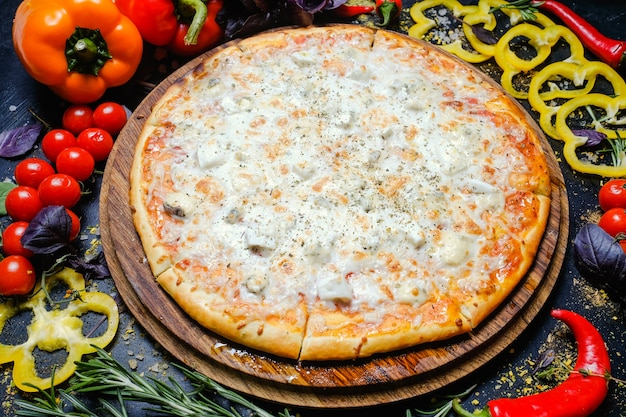 Cibo tradizionale italiano. pizza al formaggio. verdure fresche in sottofondo