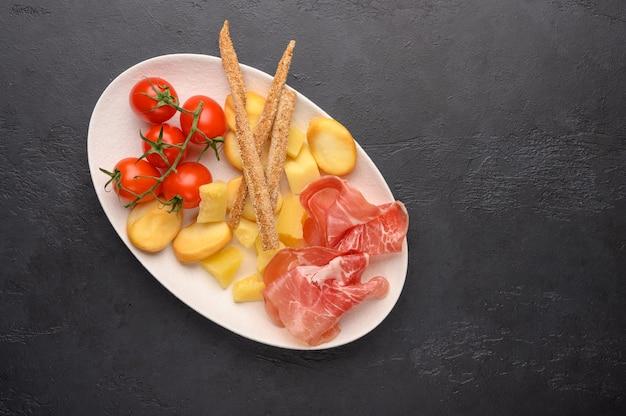 Il cibo tradizionale italiano è il pane grissini con prosciutto, formaggio e pomodori alle erbe su un piatto su uno sfondo scuro.