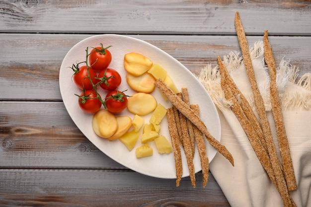 Il cibo tradizionale italiano è il pane grissini con prosciutto, formaggio e pomodori alle erbe su un piatto su un fondo di legno.