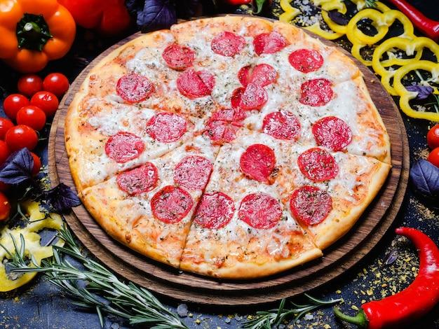 Cibo tradizionale italiano. pizza ai peperoni con formaggio fuso, verdure fresche in sottofondo