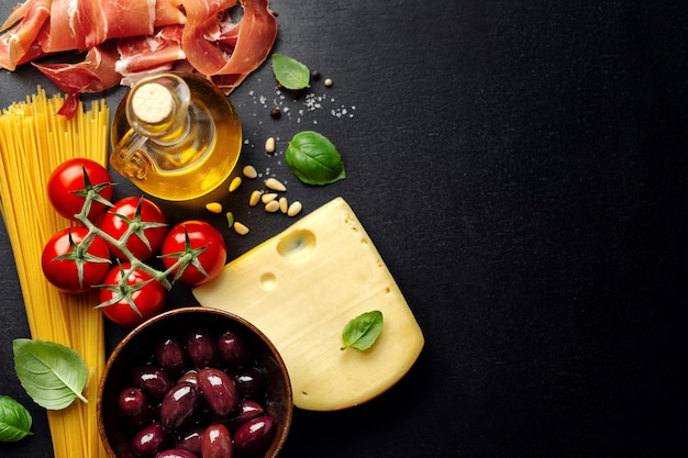 Cucina italiana tradizionale con spaghetti, pomodori, olive, olio su fondo scuro