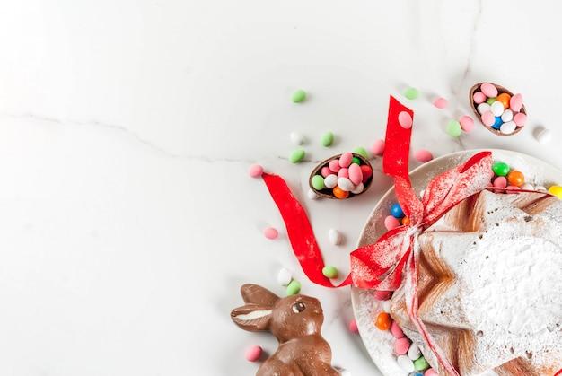 Panettone pandoro tradizionale italiano alla frutta con nastro rosso festivo, conigli pasquali e decorazioni di uova di caramella dolce, su casa in legno, vista dall'alto di copyspace