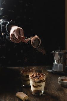 Tiramisù artigianale italiano tradizionale con mascarpone e cacao in polvere in movimento