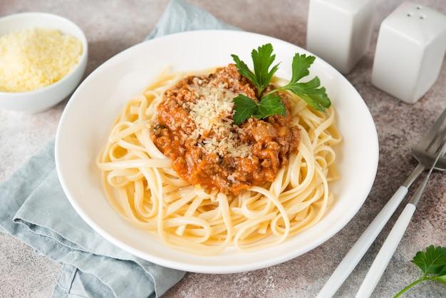 Pasta italiana tradizionale con salsa bolognese in un piatto bianco, primi piani