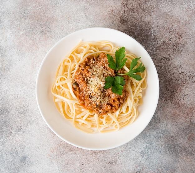 Pasta italiana tradizionale con salsa bolognese in un piatto bianco, vista dall'alto