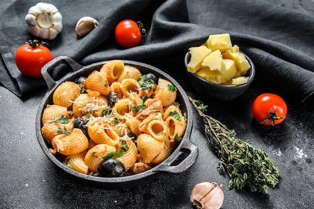Pasta italiana tradizionale con pomodoro, olive, capperi, acciughe. conchiglie rigate, puttanesca. sfondo nero. vista dall'alto.