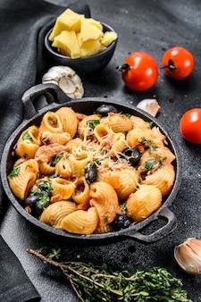 Pasta italiana tradizionale con pomodoro, olive, capperi, acciughe. conchiglie rigate, puttanesca su nero. vista dall'alto