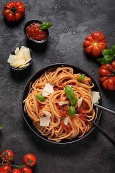 Pasta italiana tradizionale con salsa di pomodoro, basilico e formaggio su sfondo nero, vista dall'alto in basso con spazio di copia