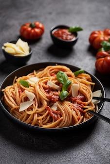 Pasta italiana tradizionale con salsa di pomodoro, basilico e formaggio sul nero, vista dall'alto in basso con spazio di copia