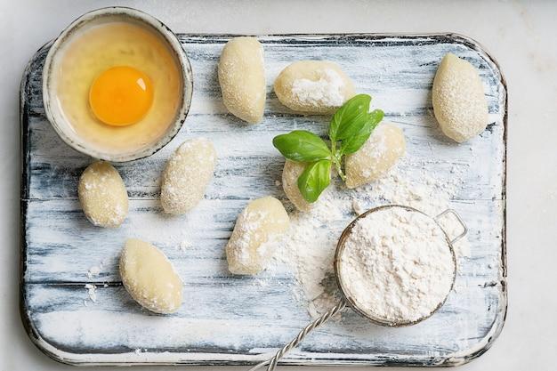 Gnocci di patate tradizionali italiani decorati con foglie di basilico, uova, farina. vista dall'alto. lay piatto