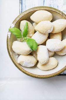 Gnocci (pasta) italiani tradizionali della patata decorati con la foglia del basilico, le uova, la farina. concetto di pasta cruda. vista dall'alto. lay piatto