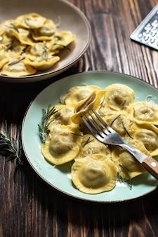 Ravioli italiani tradizionali con rosmarino e parmigiano serviti su un tavolo in legno rustico. pasta italiana