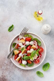 Panzanella tradizionale italiana con insalata di pomodorini, mozzarella, basilico e pane in un piatto di ceramica. vista dall'alto.